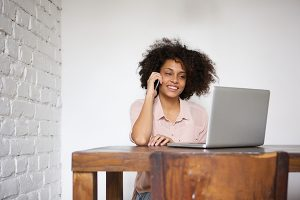 Woman working at home with laptop and mobile phone